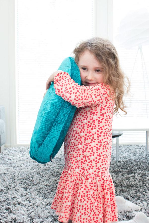 Pikkutyttö halaa Taikofon äänituntumasoitinta